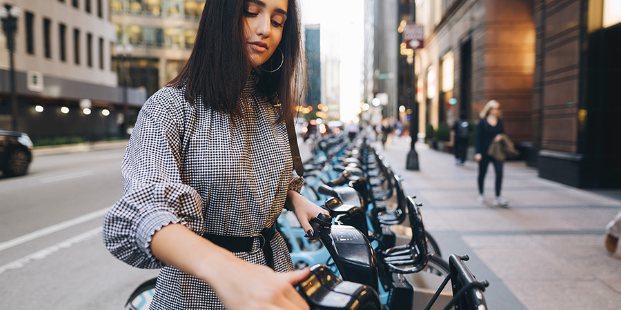 girl renting a city bike from a bike stand. What can CBD do to improve health and wellness in women?