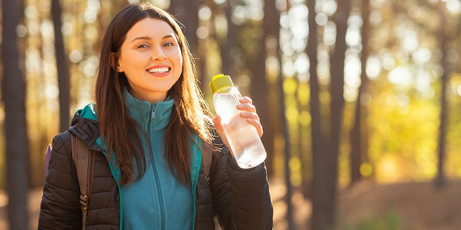 Smiling young woman drinking water while hiking. cbd for women's wellness. Buy CBD for women's issues.
