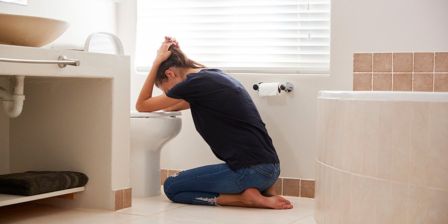 Woman suffering with morning sickness nausea in bathroom. cbd oil helps with nausea.